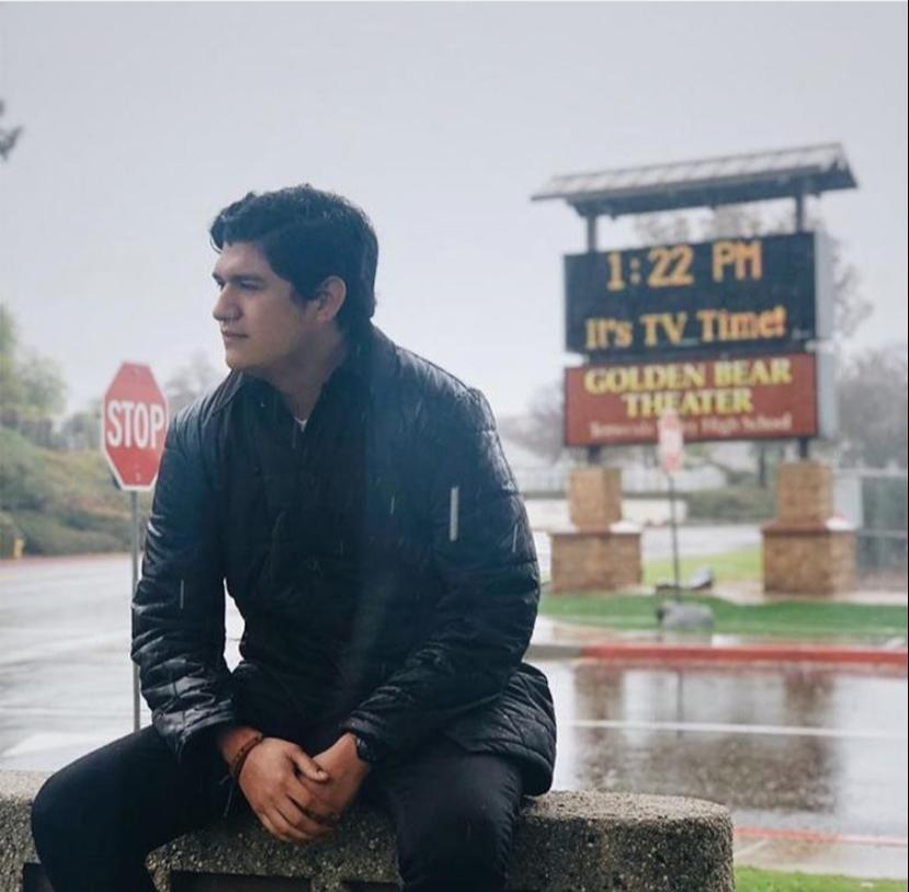 photo of Juan Gomez sitting and starting out into the distance in the rain.