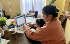 A student at a computer with a child on her lap.