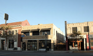 A beige brick buidling on Figueroa steet with a street light in front.