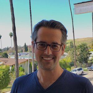 Man with glasses and dark blue v-neck shirt