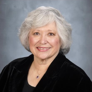 a woman with white hair and a black blazer