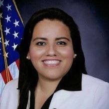 A woman with a white suit and an American flag in the background