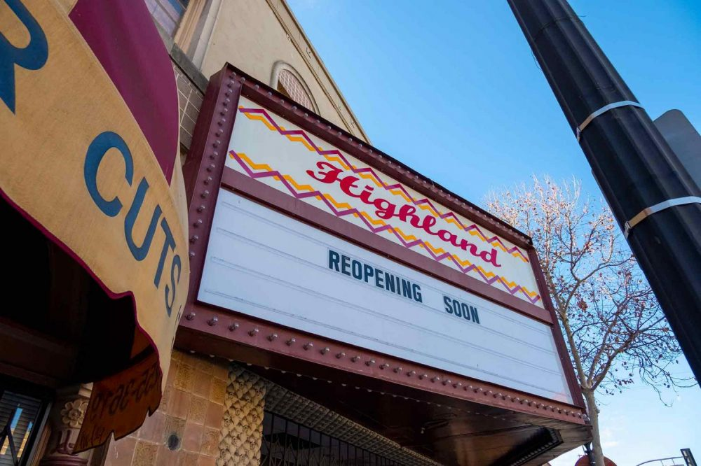 """A theater sign that says """"Highland"""" in cursive red letters"""