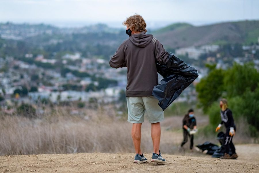 Man with trash bag stands on top of a hill