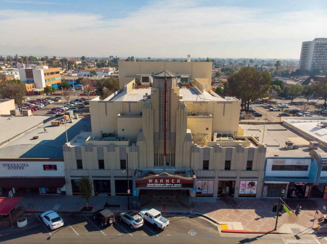 An aerial shot of a theater building with sunlight on part of it.