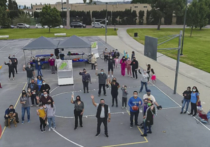 Aerial photo of people standing on a basketball court and waving