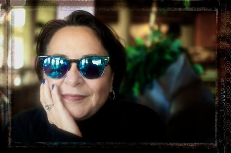 A woman smiling and wearing sunglasses, resting her chin on her hand