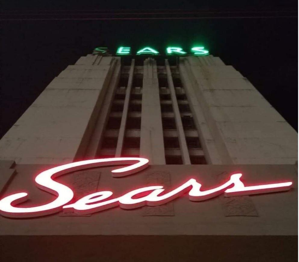 A building with a red, lit up Sears sign in cursive