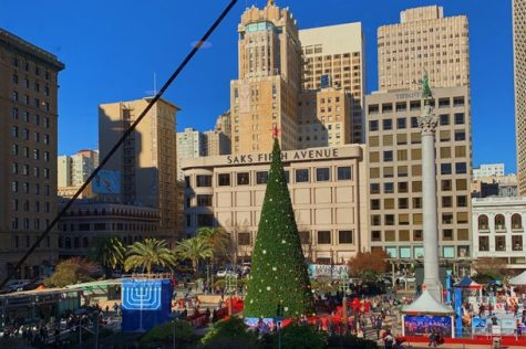 a Christmas tree and menorah in the foreground and a beige buildings against a bright blue sky