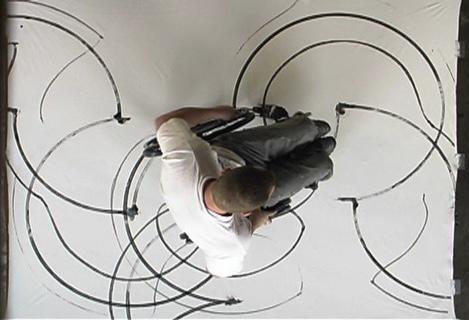 overhead shot of man in wheel chair creating artwork, black half circles on a white canvas
