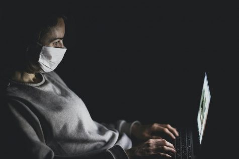 photo of man wearing a mask while on his laptop
