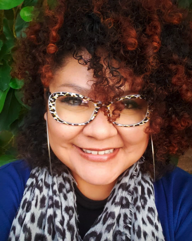 Woman with curly hair and a black and white patterned scarf and matching glasses.