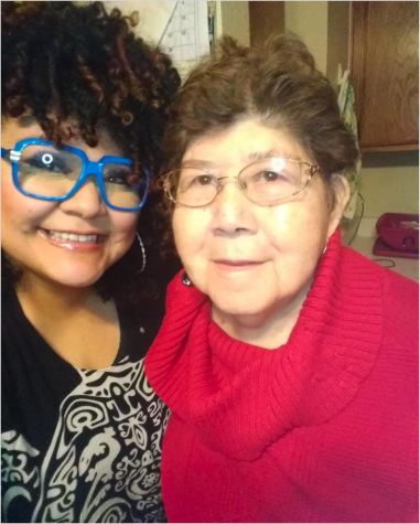 Two women side-by-side, one with blue glasses and another with a red sweater.