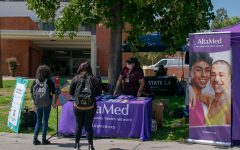 Picture shows two students in front of the AltaMed table on campus.