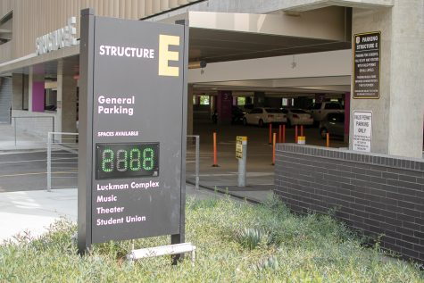 Picture shows the entrance of parking structure E. A sign pictured reads Structure E and displays the number of available parking spaces .