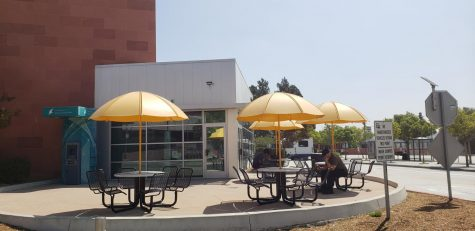 Image shows people sitting on tables outside of a closed Golden Eagle Express.