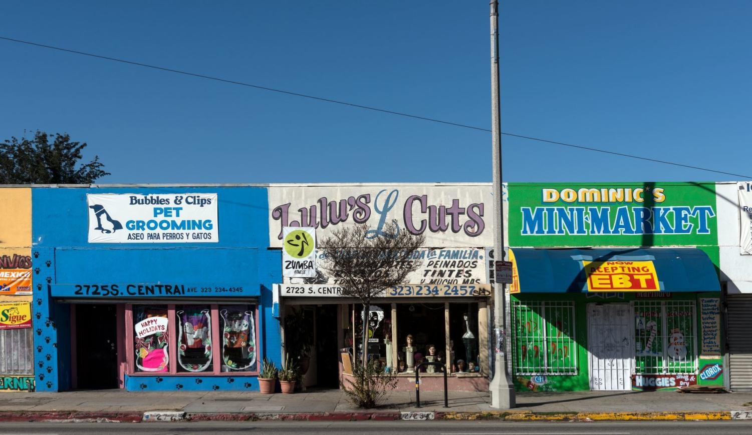"""several small attached colorful shops in a row: blue, yellow, white and green with signs such as """"mini-market"""" on them"""