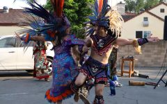 Two people in traditional clothes and colorful feather headdresses dance.