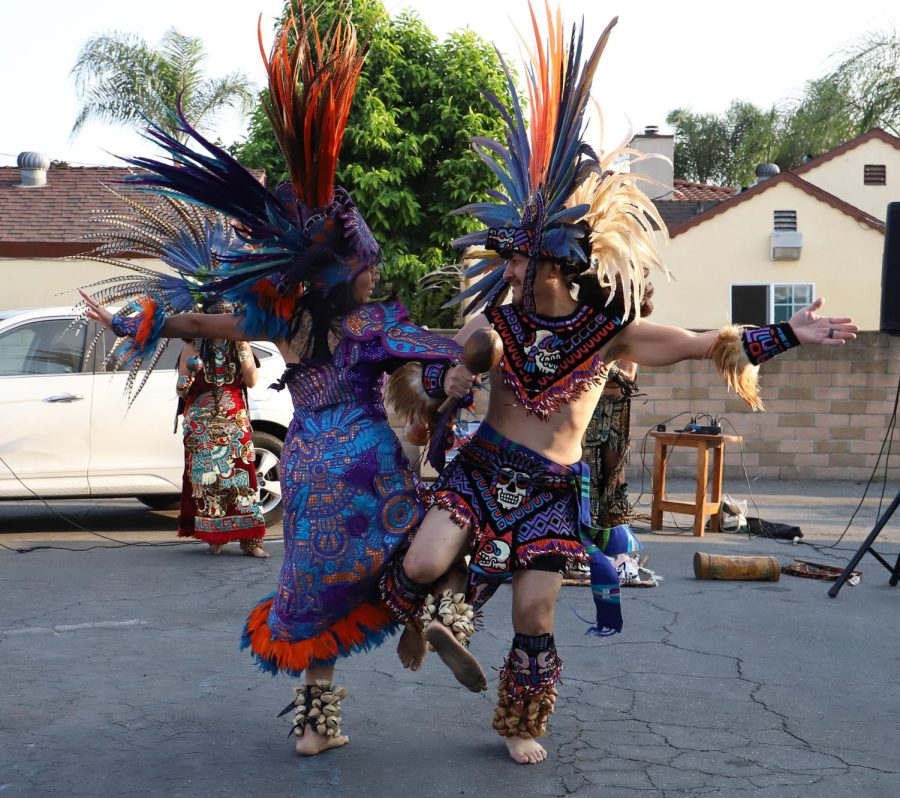 Two+people+in+traditional+clothes+and+colorful+feather+headdresses+dance.